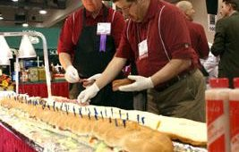 An annual treat at NAPICS are the giant subs from Sofo foods. Preparing this ginormous edition are Eric Ahlfors and Mike Schnapp.
