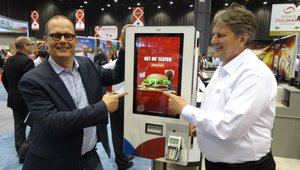 Bart Penris, left, and Frank Struwe present a QSR kiosk at the Diebold Nixdorf booth.