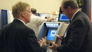 Better ATM CEO Todd Nuttall, right, explains the company's card-dispensing technology.