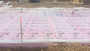 The home's slab-on-grade foundation is wrapped in a blanket of rigid foam extending completely under the slab and along the edges.