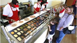 Customers at Top That! Pizza in Tulsa, Okla., go down the line telling chefs what they want on their pizzas.