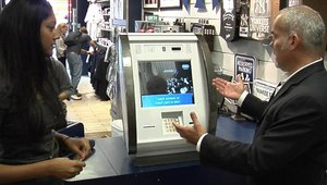 KAL ATM Software CEO Aravinda Korala demonstrates his company's new cashless Retail Transaction Machine to a customer in a Times Square store.