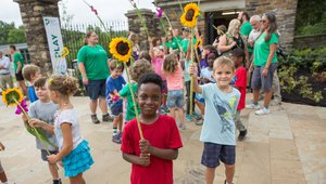 Children carried flowers in the Frick Environmental Center opening parade in 2016. Photo by Mark Simpson.