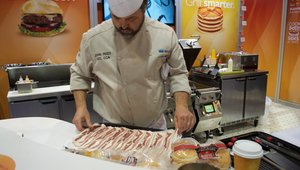 <p>A chef in the Taylor Company booth cooks bacon using the company's equipment.</p>
