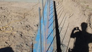 A capillary break stops water from moving from the footing up into the wall.
