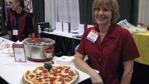 Liz Hertz of Burke Corp. offers samples of Burke's pizza toppings.